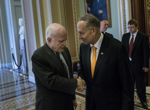 Senator John McCain (R-AZ) (L) and Senator Charles E. Schumer (D-NY) shake hands after a test vote on Capitol Hill June 27, 2013 in Washington, DC. The Senate is debating immigration reform and is expected to vote on it later today. Credit: AFP/Getty Images